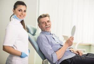 gentleman in dental chair with hygienist standing behind